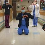 A team of 5 UNC Health employees, all wearing scrubs and disposable masks, stand or kneel feet apart from one another while forming heart symbols with their hands.